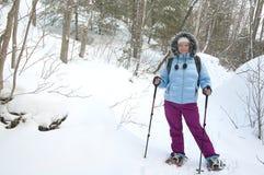 Snowshoeing in Adirondacks. Woman in blue jacket snowshoeing in Adirondacks High Peacks region in Upstate New York royalty free stock photos