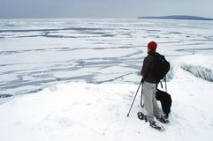Snowshoeing along Ice Flows of Georgian Bay. A snowshoe hiker and his dog stop to drink in the icy waters of Georgian Bay from Awenda Provincial Park in Ontario' Royalty Free Stock Images