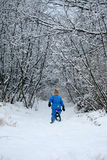 Snowshoeing on a Path. Back view of a young child snowshoeing down a snowy path Stock Photography