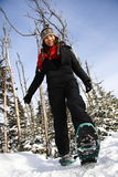 Snowshoeing in Quebec. Young woman snowshoeing in pine forest near Baie Saint-Paul, Quebec, Canada Royalty Free Stock Photography