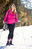 Snowshoes, active smiling woman in the snow. Winter sports. Hiking in the snow. Snowshoes at the foot of a smiling young woman on vacation. sunglasses and winter Stock Photo