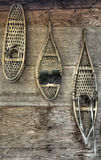 Snowshoes on a cabin wall. Three different pairs of old-fasioned snowshoes hanging on a cabin wall Stock Photos