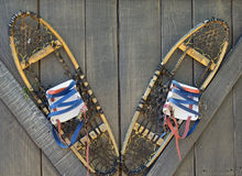 Snowshoes hanging on a wall. Old snowshoes mounted on a wooden wall stock images