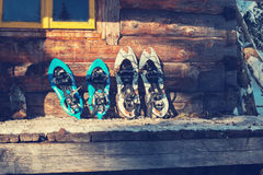 Snowshoes are on the porch of an old log cabin. Close up Stock Image