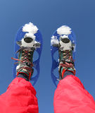 Snowshoes and Red Ski suit in the mountains Royalty Free Stock Images