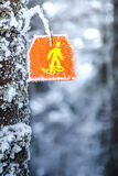 Snowshoes sign hiking marker on tree in winter forest trail Stock Photo