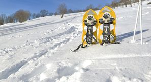 Snowshoes and sticks on the snow. Y hill under blue sky stock photo