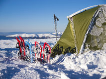 Snowshoes and tent in the mountains. Royalty Free Stock Images