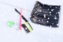 Snowshowel nero con la maniglia di legno nel mucchio della neve Fotografia Stock