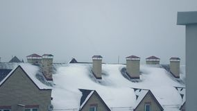 Snowstorm against sloped roofs of residential houses in winter 4K pan video. Snowstorm against sloped roofs of residential houses in winter 4K pan shot stock video footage