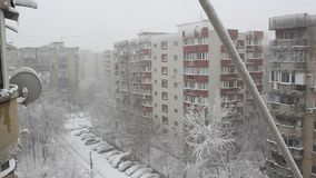 Snowstorm between blocks of flats. TV antenna covered with snow stock video
