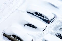 After a snowstorm, cars in the parking lot are covered with a th Royalty Free Stock Photo