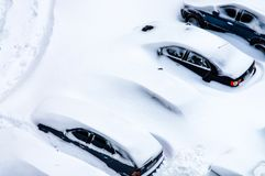 After a snowstorm, cars in the parking lot are covered with a th Royalty Free Stock Image