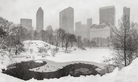 Snowstorm in Central Park with Midtown skyscrapers. New York City. Frozen pond and heavy snowfall in Central Park with a panoramic view of Manhattan skyscrapers Stock Photos
