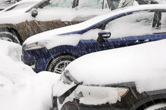 Snowstorm at city car park. Details of three cars with doors, headlights and rear view mirrors covered with thick layer snow during snowstorm. Shallow depth royalty free stock images