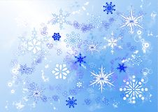 Snowstorm. A drawing of swirling snowflakes in various sizes and designs on a blue background Stock Image