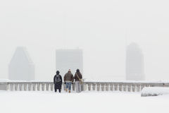 Snowstorm in Montreal city. 3 tourists looking at Montreal downtown under a snowstorm during winter Stock Image