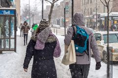 Snowstorm in Montreal. Pedestrians on Mont-Royal Avenue stock image