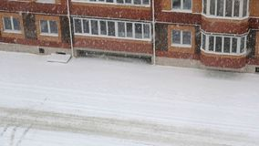 Snowstorm. Multi-storey building on the courtyard. Snowstorm. View from the window of multi-storey building on the courtyard and the road of the neighborhood stock video footage