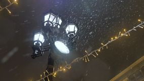 Snowstorm during the New Year holidays. Street lamp shines on snowflakes. View from the bottom stock video footage