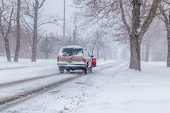 Snowstorm at non urban area. A snowplow truck passing a road stock photo