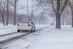 Snowstorm at non urban area. A snowplow truck and a plice passing a road royalty free stock image