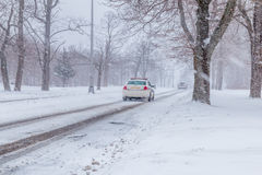 Snowstorm at non urban area. A snowplow truck and a plice passing a road royalty free stock photos
