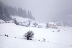 Snowstorm over mountains and alpin village in winter, Alps, Swit Royalty Free Stock Image