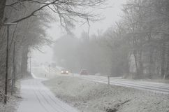 Snowstorm on the road. Sparce traffic moving slowly, on a road during heavy snowfall that causes reduced visibility Royalty Free Stock Photos