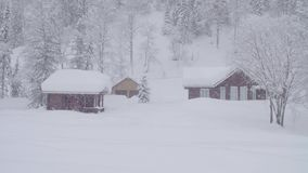 Snowstorm in skitouring lodge in Siberia. Houses covered with snow stock video