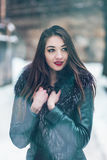 Snowtime stående av den härliga brunettflickan Arkivfoto