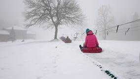Snowtube felice di giri del mather e della ragazza sulle strade nevose stock footage