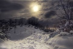 Snowy и замороженная верхняя часть холма с пасмурным ночным небом и лунного света с городом освещают на предпосылке Лес в Словаки стоковые изображения