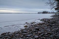 Snowy трясет на береге и замороженном озере в зиме Стоковая Фотография