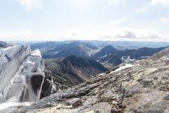 Snowy трясет на переднем плане и огромная гора на заднем плане в горах субполярного Урала Стоковая Фотография
