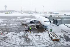 Snowy airport, airplane, personal and service cars Royalty Free Stock Image