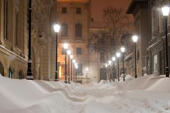 Snowy alley at night. Snowy alley with old imposing buildings in lamps light Royalty Free Stock Images