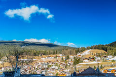 Snowy alpine village. In Italy illuminated by sun with mountains in the background Royalty Free Stock Photography