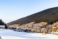 Snowy alpine village. In Italy illuminated by sun with mountains in the background Stock Image