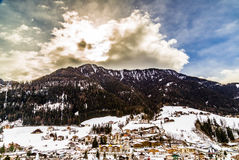 Snowy alpine village. In Italy illuminated by sun with mountains in the background Stock Photo
