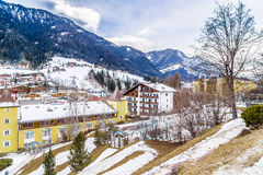 Snowy alpine village. In Italy illuminated by sun with mountains in the background Royalty Free Stock Photo