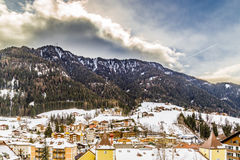 Snowy alpine village. In Italy illuminated by sun with mountains in the background Stock Photos