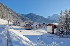 Snowy alpine village in Italy illuminated by sun with mountains in the background. Ski Resort of Canazei, Italian Dolomites, Trentino-Alto-Adige region, Italy Stock Image