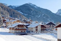 Snowy alpine village in Italy illuminated by sun with mountains in the background. Ski Resort of Canazei, Italian Dolomites, Trentino-Alto-Adige region, Italy Royalty Free Stock Image