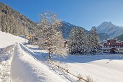 Snowy alpine village in Italy illuminated by sun with mountains in the background. Ski Resort of Canazei, Italian Dolomites, Trentino-Alto-Adige region, Italy Royalty Free Stock Photography