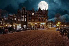 Snowy Amsterdam by night in the Netherlands. By full moon Stock Image