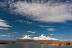 Snowy Ararat mountain in blue sky with foamy clouds. Blue lake with reeds and white Ararat mouantain with snow and cloud on it Stock Images