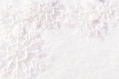 Snowy background. Group of snowflake decorations resting in fresh snow forming a border Stock Images