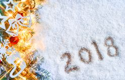 Snowy background with decorated fir tree and inscription `2018` Royalty Free Stock Image