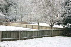 Snowy Backyard. Snow falling in a backyard with trees and fences Stock Photos